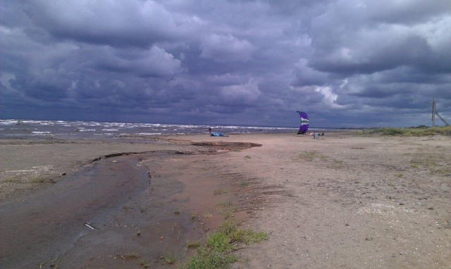 Några kite-surfare var de enda som hade hittat ut i den friska vinden, åskan lurade vid horisonten