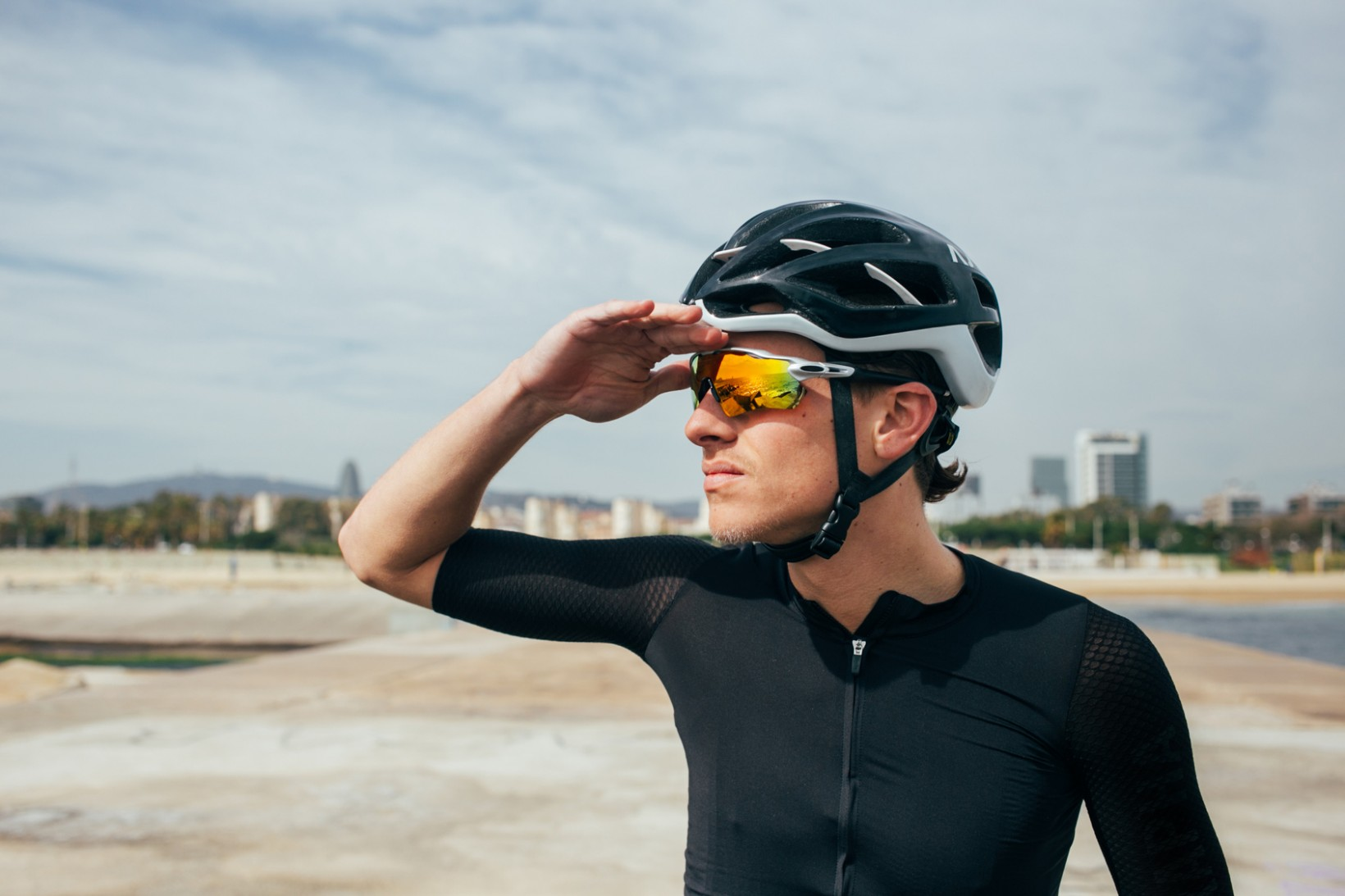 Professional cyclist in all black looks into the distance wearing yellow lenses in glasses with city out of focus in the background