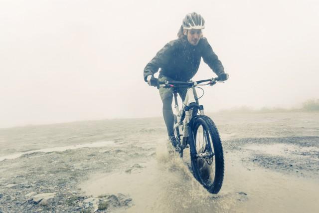 Mountain Biker Racing Through Puddle